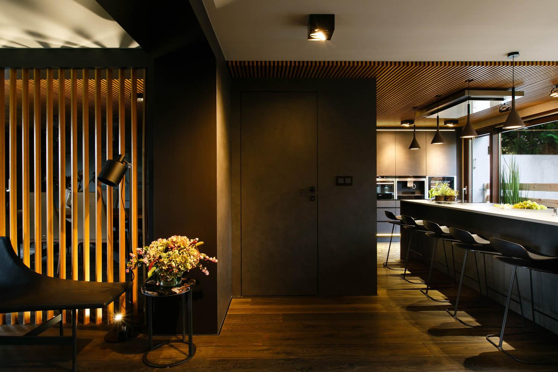 Duży, designerski fotel, szezlong w korytarzu. Mieszkanie utrzymane w ciemnym klimacie. Piękny projekt.