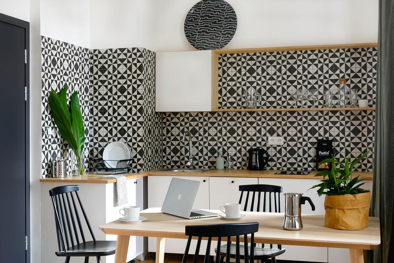 Czarno-biała kuchnia z moizaiką na ścianie. Dobre zdjęcie kuchni.