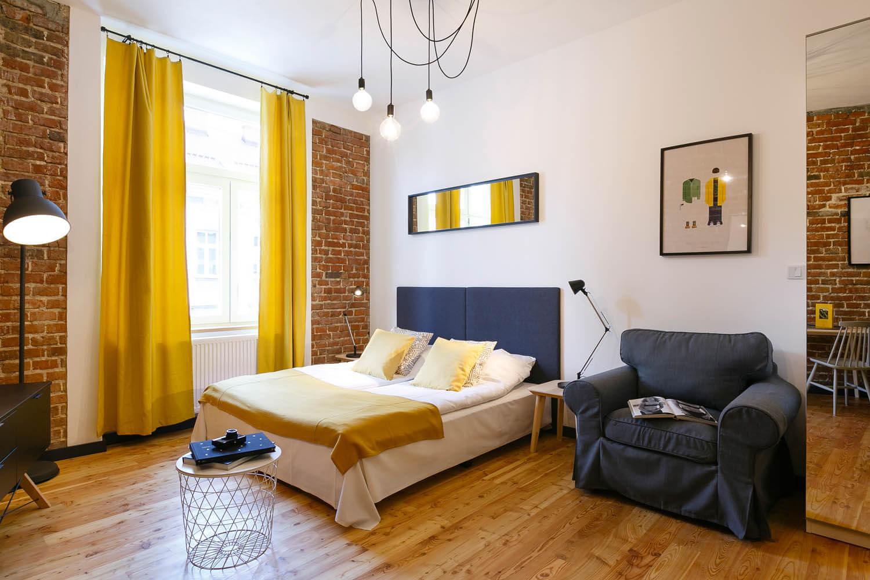 Żarówki zwisają z sufitu. Żółte zasłony w sypialni
