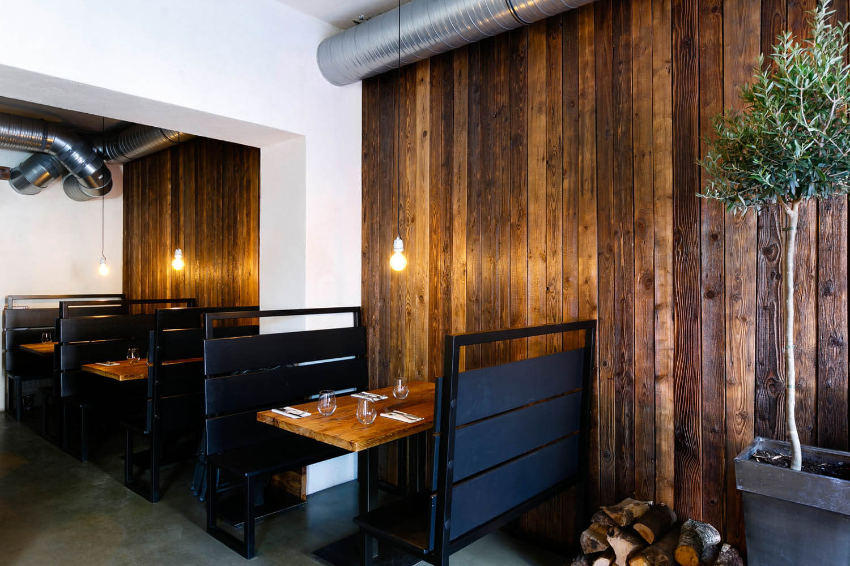 Wnętrze włoskiej restauracji. Długie deski na ścianach.
