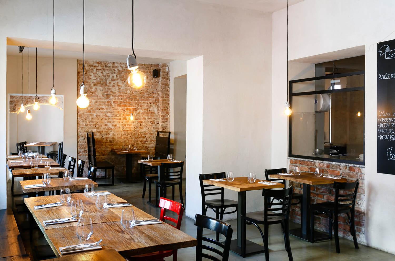 Surowe wnętrze włoskiej restauracji w Krakowie. Gołe ściany, nagie żarówki zwisają z sufitu