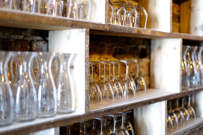 Szklanki i kieliszki ustawione rządkiem we wnętrzu włoskiej restauracji w Krakowie