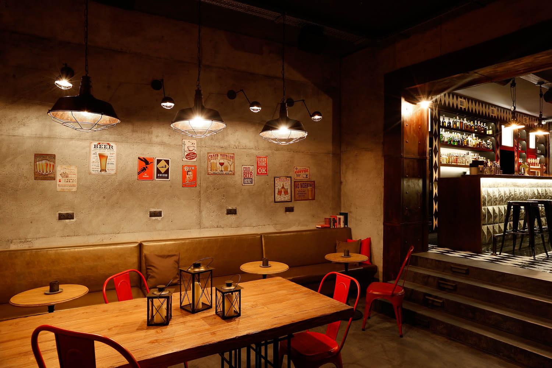 Zdjęcie wnętrza pubu w Krakowie. Czerwone krzesła, długi bar.