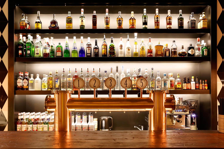 Zbliżenie na alkohole w pubie w Krakowie. Dużo alkoholi, krany do piwa