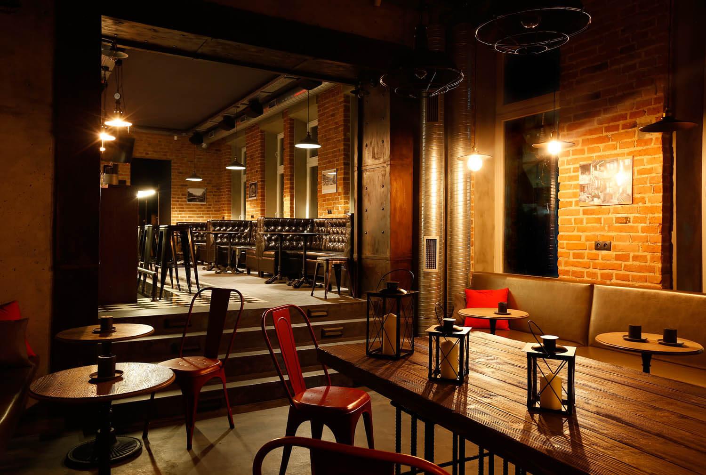 Wnętrze pubu w Krakowie. Cegła na ścianach, czerwone krzesła, designerskie lampy.